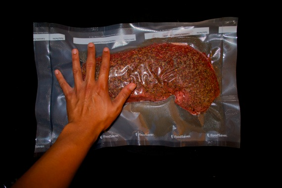 Vacuum packed top round beef with hand